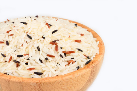 Raw rice in the wood bowl on white background
