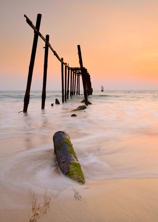 Wood bridge with seascape at sunset and motion wave