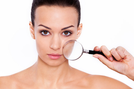 facial features: Magnifying facial features. Studio shot of a beautiful woman with a magnifying glass in front of her face