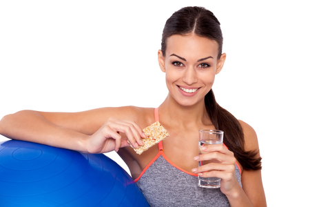 Gezonde voeding na de training is de weg naar succes! Bijgesneden opname van aantrekkelijke sportieve vrouw zat naast haar fitness bal en met een eiwit bar met een glas water.