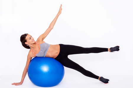 Fitness is fun! Portrait of an attractive young woman using a fitness ball for an upper body workout ovet white isolated background. Stok Fotoğraf