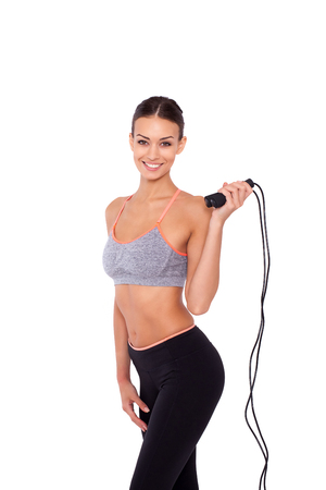 skipping rope: Skipping rope is her way to fitness. Portrait of an attractive young sporty woman holding a skipping rope while standing over white isolated background.