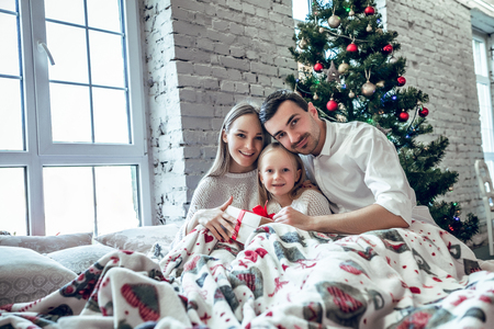 Family sitting on bed near X-mas tree. Mother, father and baby having fun in bedroom. People relaxing at home. Winter holiday Xmas and New Year concept