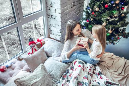 Girl holding gift box smiling and sending present to mom. Happy child girl near a Christmas tree with Christmas present bought from shopping sale. xmas holiday sending gift. top view