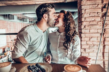 Cheerful mood. A couple in love is enjoying each other while sitting in a cafe.