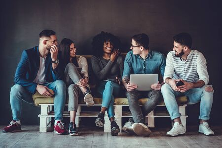 Happy diverse friends group sharing social media app news sitting holding phones, smiling multiracial young people students showing funny videos on laptop.