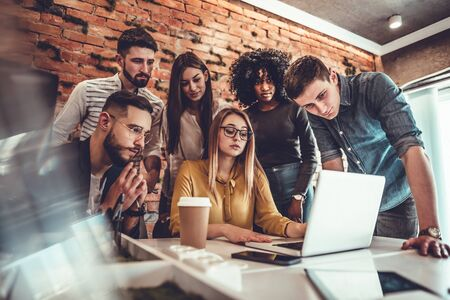 Perfect creative team. Group of six cheerful young people looking at laptop with smile while leaning to the table in office. Stock Photo