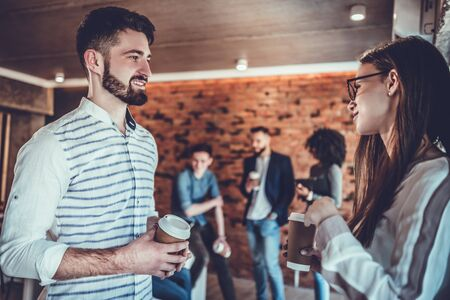 Sharing great ideas. Happy young woman and young man holding cups of coffee and discussing something while standing together near the wall in office