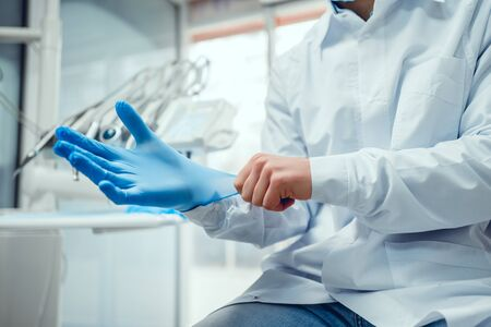 Close up view of male doctor's hands putting on blue sterilized surgical gloves in the medical clinic.