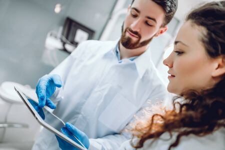 Smiling dentist and female patient looking at digital tablet during treatment in dental clinic. selective focus.