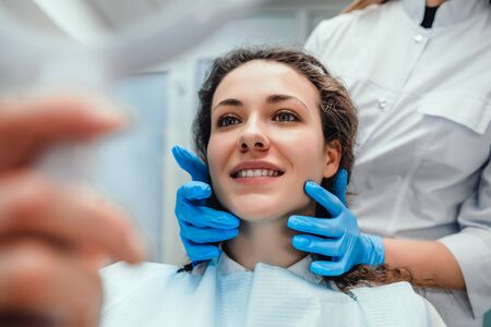 Healthcare and medicine concept.Happy woman patient looking in the mirror at the teeth, sitting in the dental chair. selective focus.