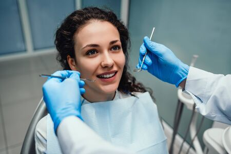 Young beautiful woman with beautiful white teeth sitting on a dental chair. Portrait of a woman with toothy smile sitting during examination at the dental office.