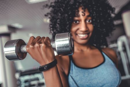 Portrait of smiling african women looking camera in gym lifting dumbbell. Yong black sportive girl with curly hair on training biceps