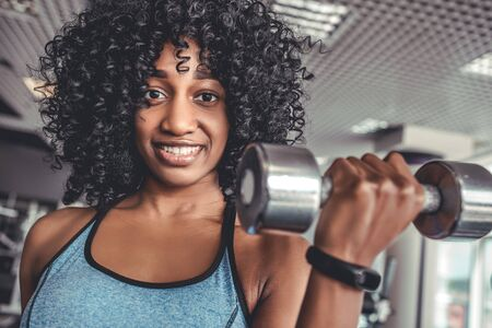 Portrait of cheerful african young woman with activity tracker on hand doing exercise with dumbbels in gym. Muscular body and wellbeing concept 스톡 콘텐츠