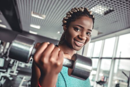 Portrait of sportive african girl lifting metall dumbbell on training in gym 스톡 콘텐츠