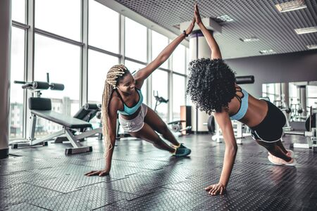 Sporty women giving high five to each other while working out making push ups together at gym.