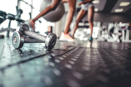 Image with focus on dumbbells on a dark flor in fitness gym with women legs in blurred background