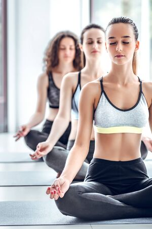 Three beautiful young women standing in lotus position on the mat at the gym. close up view. vertical photo