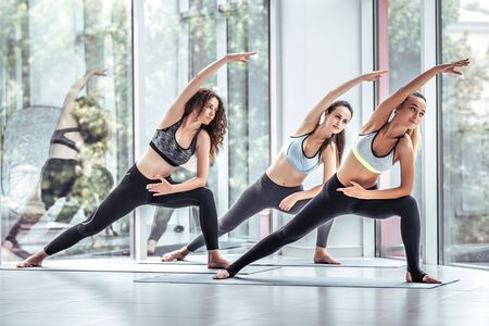 Group smiling yoga women doing exercise in gym. Yoga team in gym class. Young girls, sport, training, yoga concept