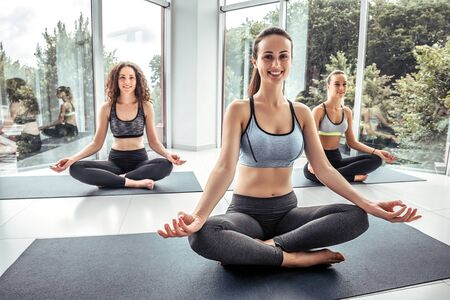 Women practicing yoga together and sitting in the lotus pose: mindfulness meditation, spirituality and healthy lifestyle concept Stockfoto