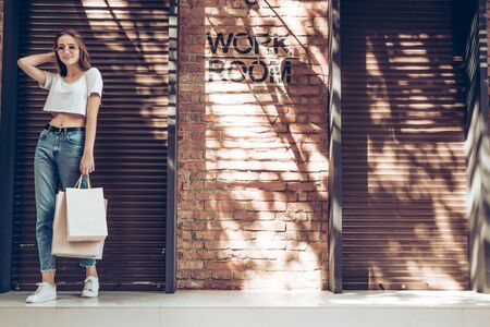 Young smiling girl with shopping bag wearing white t-shirt and blue jeans near brick wall.Lifestyle concept.