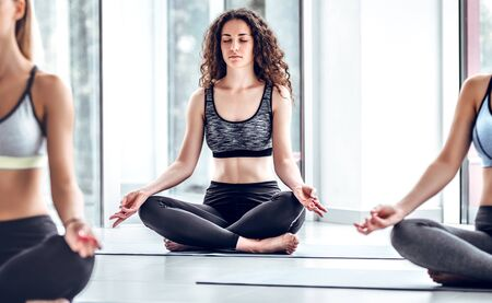 Young woman in yoga class doing meditation lotus pose. Group of healthy people meditating in a yoga studio. Close up