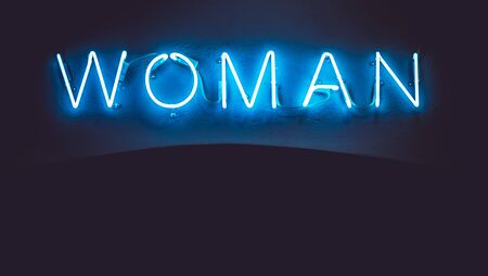 Blue neon sign of the word Woman on a black background.