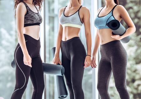 Group of female friends in sportswear smiling together while standing in a gym after yoga workout. Women standing by panoramic windows with exercise mat. Stockfoto
