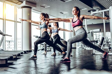Sportive young women in a gym training. Working out in a fitness gym. Side view. Stockfoto