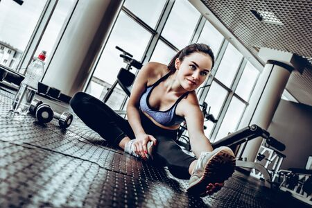 Fitness woman at stretching training at gym. Young slim girl makes aerobics exercise sitting on floor . Healthy lifestyle, gymnastics concept.