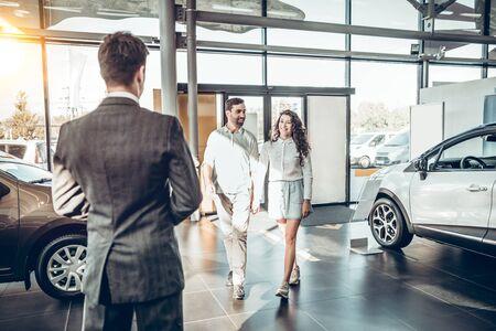 junge Familie kommt zum Autohaus, um das Auto auszuwählen, um es zu kaufen. Manager trifft ein junges Paar im Autohaus Standard-Bild