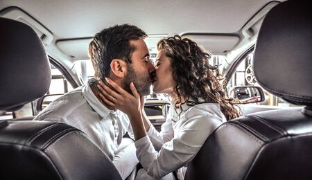 Happy beautiful couple in love kissing in a new car in car dealership.