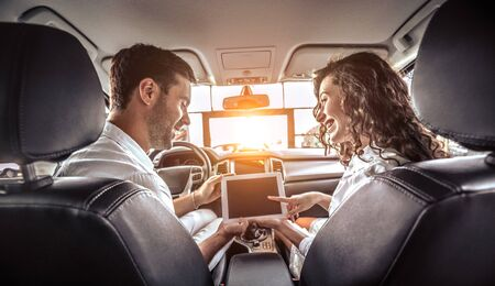 Couple is looking on tablet in a new car. The are looking options of brandnew car. young family wants to buy a car at the car dealership. Rear view
