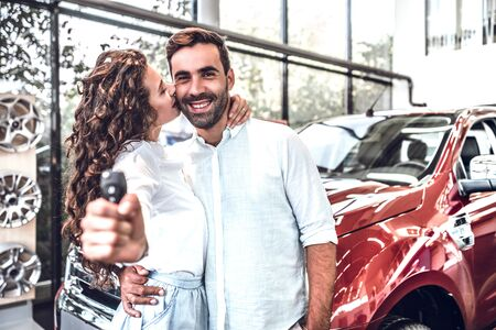 Key from a new car. Young couple standing near then new car and holding a key. woman is kissing her husband in cheek