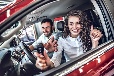 Close up of a happy young couple smiling showing car keys and thumbs up in a new car at the dealership. selective focus