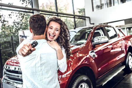 Smiling couple hugging and holding their new key at new car showroom.