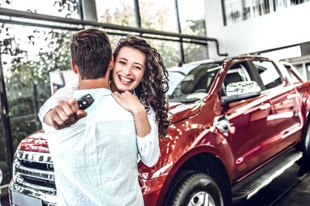 Happy young hugging couple chooses and buying a new car for the family in the dealership