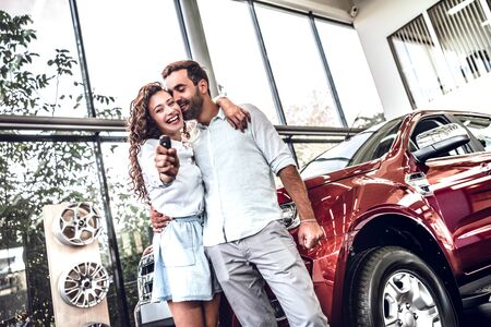 Young couple with keys to new car. Beautiful couple is hugging and smiling, man is kissing her wife in cheek