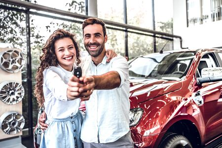 First big buy together. Portrait of a happy young couple hugging in a car salon showing car keys to a newly bought vehicle. 스톡 콘텐츠