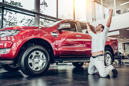 Happy owner of new automobile kneeling, posing and holding hands up. Bearded man standing on knees before red big car. Customer buying vehicle in modern car dealership.