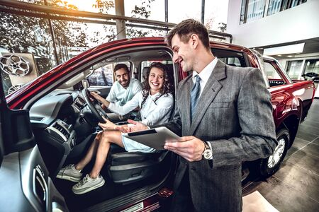 lucky family sitting in new automobile in auto salon, examine auto, speaks with car dealer about technical condition machine