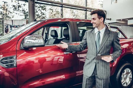 Salesman stay near car. He is waiting for clients. Car is red. He holds tablet in hand. He is smiling. He shows with his hand on brandnew car