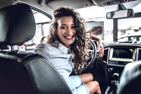 Beautiful young happy woman posing inside of the new car. 스톡 콘텐츠