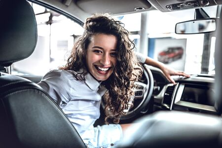 Portrait of beautiful happy young woman inside in new car.