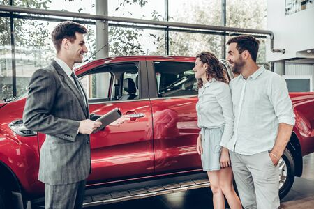 Attractive couple is talking to car sales manager in luxury car dealership and looking at beautiful red automobile. Luxurious autos and people concept.