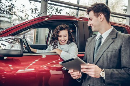 Car info. Happy young woman sitting in a new car at car salon professional salesman showing them information on digital tablet couple buying a car service help communication clients business concept