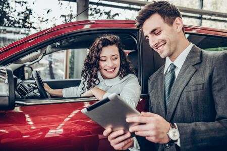 Car salesman giving explanations on tablet to pretty young woman. Close up view 스톡 콘텐츠