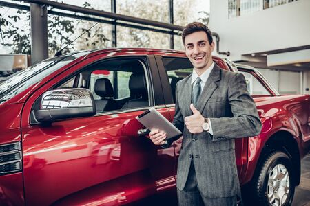 Handsome smiling salesman in formal wear with tablet in hand looking on camera and shows thumb up on new car background.