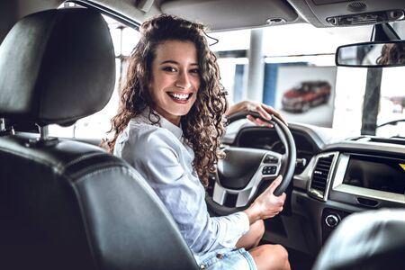 Happy woman inside car in auto show or salon. 스톡 콘텐츠