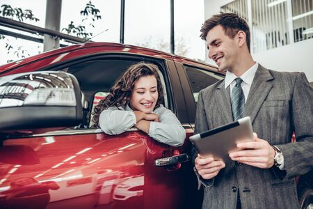 Beautiful young woman is talking to handsome sales manager while choosing a car in dealership. Man is using a digital tablet